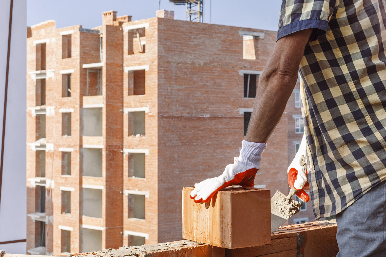 Bricklayer in protective gloves with a trowel installing a brick on the mortar on the wall on the background of a multi-storey building