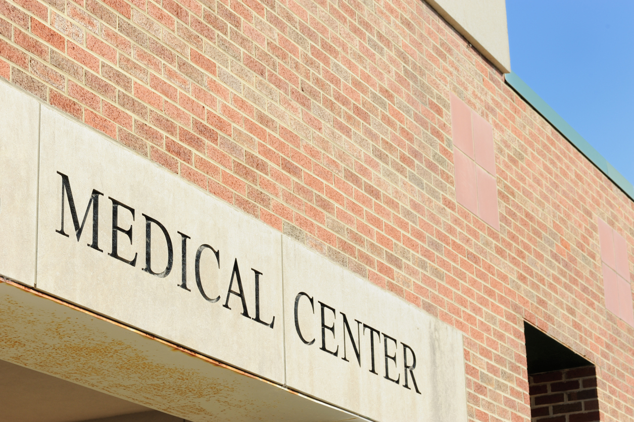 Photograph of medical center with engraved sign and brick wall.  Image is horizontal composition.